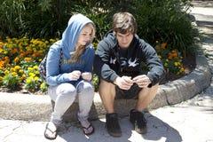 Couples d'adolescent se reposant sur la bordure de trottoir Photos stock