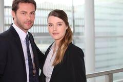 Couples d'affaires devant l'hublot Photographie stock