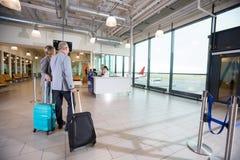 Couples d'affaires marchant vers la réception dans l'aéroport images libres de droits