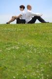 Couples d'affaires se reposant de nouveau au dos sur l'herbe Image libre de droits