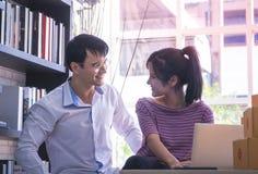 Couples d'affaires vérifiant des actions dans leurs affaires à la maison en ligne images stock