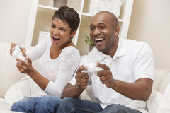 Couples d'afro-américain ayant l'amusement jouant le jeu visuel de console images stock