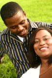 Couples d'Afro-américain détendant sur l'herbe Photographie stock