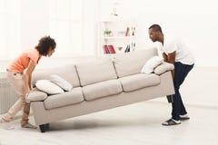 Couples d'afro-américain plaçant le sofa à la nouvelle maison photographie stock libre de droits