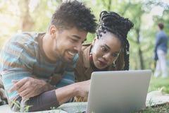 Couples d'afro-américain regardant l'ordinateur portable images stock