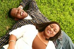 Couples d'Afro-américain s'étendant sur l'herbe Photo libre de droits