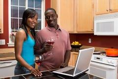 Couples d'Afro-américain utilisant l'ordinateur portatif dans la cuisine Photos stock