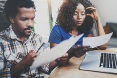 Couples d'afro-américain vérifiant les factures à la maison ensemble à la table en bois Jeune homme de couleur et son amie à l'ai Photo libre de droits