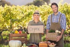 Couples d'agriculteur tenant un panier et un signe organique Photos libres de droits