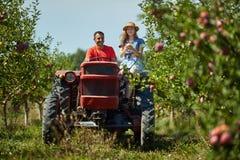 Couples d'agriculteurs conduisant le tracteur image stock