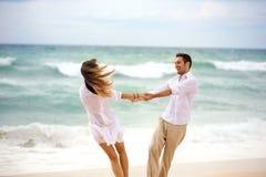 Couples d'amour ayant l'amusement de g sur la plage Photographie stock libre de droits