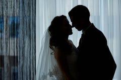Couples d'amour de silhouette sur une fenêtre de fond Images stock