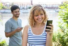 Couples d'amour envoyant le message avec le téléphone portable images stock