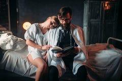 Couples d'amour lisant un livre dans la chambre d'hôpital Photo stock