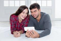 Couples d'amour regardant la TV au téléphone Photographie stock