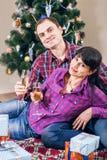 Couples d'amour sous l'arbre de Noël avec du vin Photo libre de droits