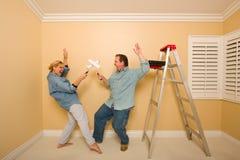 Couples d'amusement jouant le combat d'épée avec des rouleaux de peinture Image stock