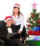Couples d'amusement regardant dans l'ordinateur portable prèsde l'arbre de Noël Photos stock