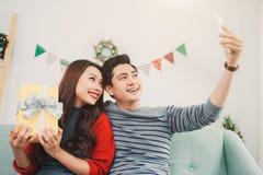Couples d'Asiatique de Noël Un homme bel donnant son amie/wif Images stock