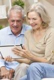 Couples d'homme aîné et de femme sur l'ordinateur de tablette Photos libres de droits