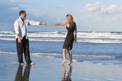 Couples d'homme et de femme ayant la danse d'amusement sur une plage Photos stock