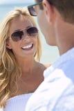 Couples d'homme et de femme dans des lunettes de soleil à la plage Image stock