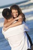 Couples d'homme et de femme dans l'étreinte romantique sur la plage Image libre de droits