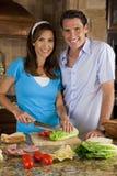 Couples d'homme et de femme dans la cuisine avec de la salade Photos stock