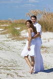 Couples d'homme et de femme marchant sur une plage vide Image libre de droits