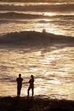 Couples d'homme et de femme sur la plage au positionnement du soleil Photographie stock libre de droits