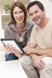 Couples d'homme et de femme utilisant l'ordinateur de tablette à la maison Photos stock