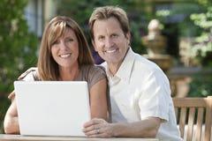 Couples d'homme et de femme utilisant l'ordinateur portable dans le jardin Image stock
