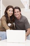 Couples d'homme et de femme utilisant l'ordinateur portable à la maison Photo stock