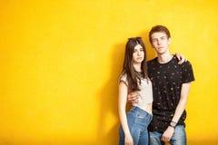 Couples d'Inlove posant dans le style de mode sur le mur jaune Image stock
