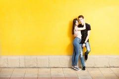 Couples d'Inlove posant dans le style de mode sur le mur jaune Photos stock