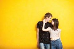 Couples d'Inlove posant dans le style de mode sur le mur jaune Photo stock