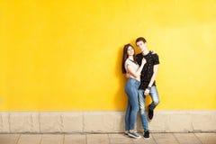 Couples d'Inlove posant dans le style de mode sur le mur jaune Photographie stock