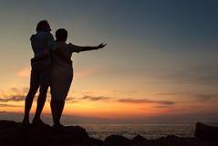 Couples d'Inlove sur le littoral au temps de coucher du soleil Photographie stock