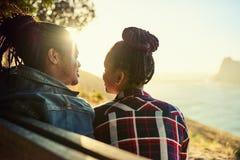 Couples d'origine africaine se reposant sur un banc public de point de vue Photos stock