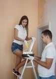 Couples d'Oung peignant le mur intérieur de la nouvelle maison Image stock