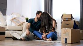 Couples d'Oung se déplaçant la nouvelle maison Se reposer sur le plancher et détente images stock