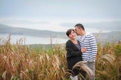 Couples d'une cinquantaine d'années attrayants affectueux regardant tendrement l'un l'autre dans l'herbe d'automne images libres de droits