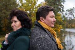 Couples d'une cinquantaine d'années dans l'expression de forêt d'automne des sentiments Images stock