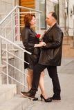 Couples d'une cinquantaine d'ann?es dans int?gral sur une rue de ville pendant l'?t? dans la lumi?re de coucher du soleil Un homm image stock