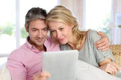 Couples d'une cinquantaine d'années à la maison utilisant le comprimé Image stock
