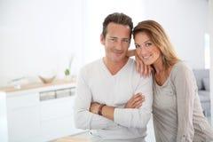 Couples d'une cinquantaine d'années affectueux dans la maison toute neuve Image libre de droits