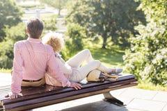 Couples d'une cinquantaine d'années détendant sur le banc de parc photos libres de droits