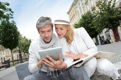 Couples d'une cinquantaine d'années de fantaisie visitant et à l'aide du comprimé en ville Photographie stock