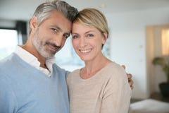 Couples d'une cinquantaine d'années de sourire à la maison Photo stock
