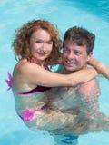 Couples d'une cinquantaine d'années de sourire dans une piscine Photos libres de droits